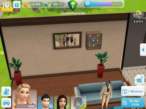 Tippe den Bilderrahmen in Die Sims Mobile an, um deine Sims im Überblick zu sehen
